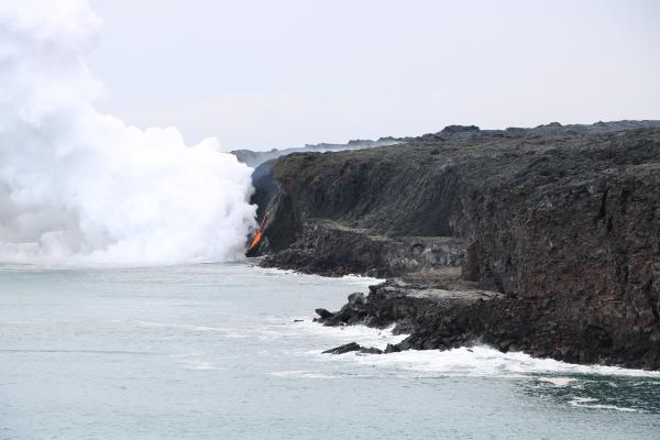The rocky shelf at the base of the sea cliff is all that remains of the Kamokuna lava delta following the New Year's Eve collapse. (USGS HVO)