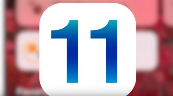 An iOS 11 logo is on display having an iPhone as its vague background. (YouTube)