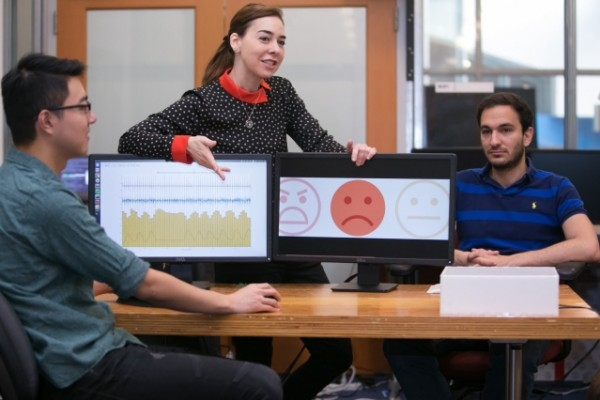 Professor Dina Katabi (center) explains how PhD student Fadel Adib's (right) face is neutral but that EQ-Radio's analysis of his heartbeat and breathing show that he is sad.